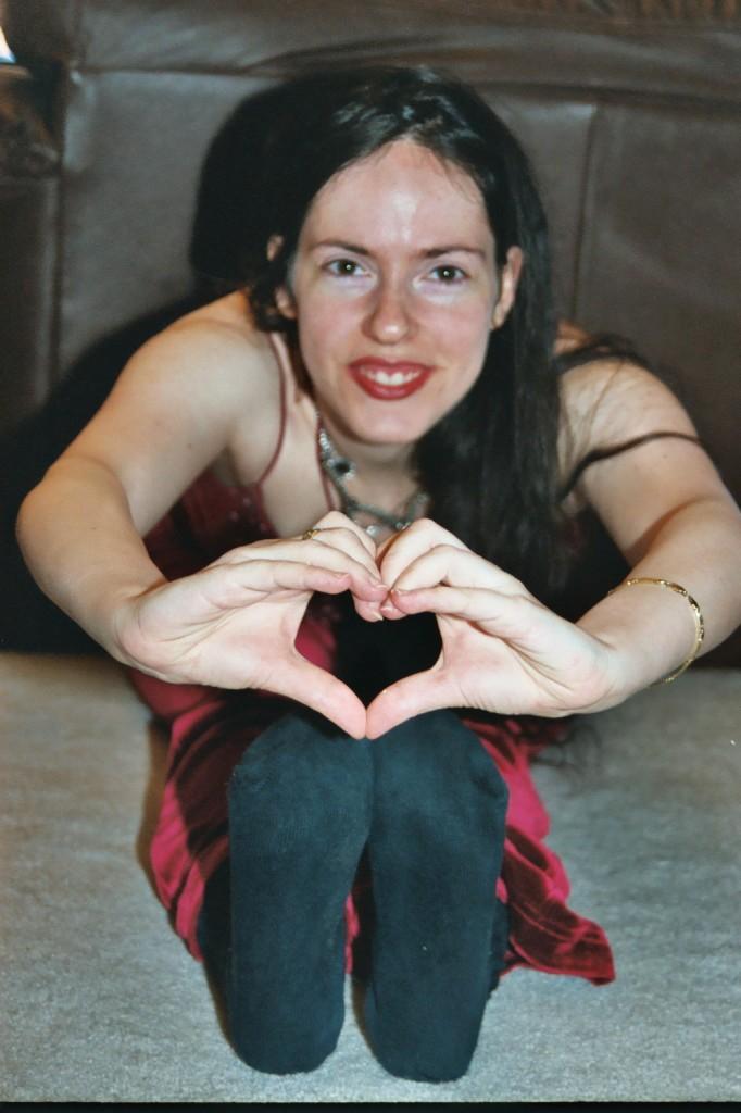 Lehavi, doing the trademark heartMark heart hand gesture in yoga stretch