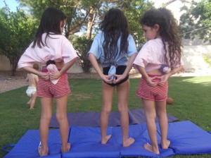 Heart Hands upside down on back of three girls