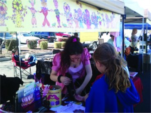 Tali Lehavi sells HeartMark jewelry called the T Sponap to fifth grade girls at the Farmer's Market Store