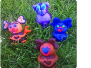 Figurines from fimo clay that make the trademark heart hand gesture called the HeartMark that is available for license by Tali Lehavi