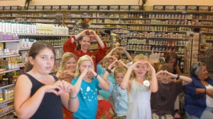 Children learning HeartMark Health at Sprouts Supermarket, doing the Heart Hand gesture as they learn